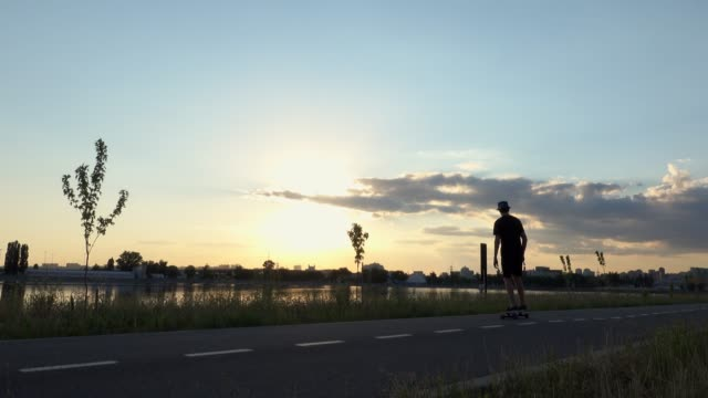 Unrecognizable silhouette view young hipster man riding longboard skating enjoying cruising on beautiful countryside road in sunset with beautiful sky.