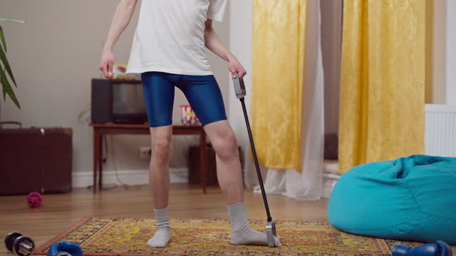 unkenntlich dünn retro mann tun aerobic mit widerstandsband in innenräumen. junge schlanke kaukasische kerl ausbildung zu gymnastik musik und tanzen zu hause in den 1980er oder 1990er jahren. lifestyle und sport - fitnessausrüstung stock-videos und b-roll-filmmaterial