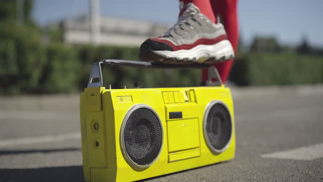 Unrecognizable slim woman in red legging and sneakers stomping on vintage yellow tape recorder. Unknown sportswoman with retro musical device in sunlight outdoors. Disco music concept.
