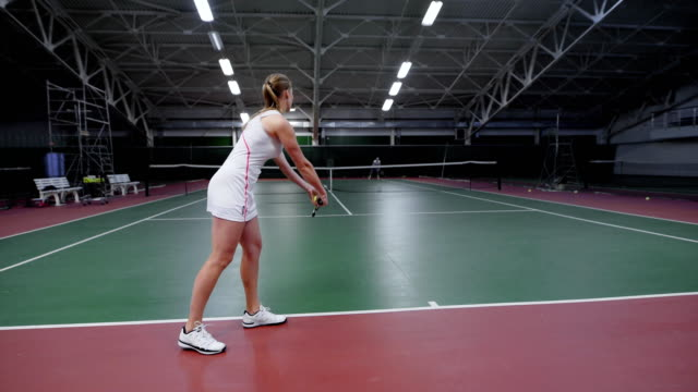 Unrecognizable sportswoman standing on tennis court and playing match video