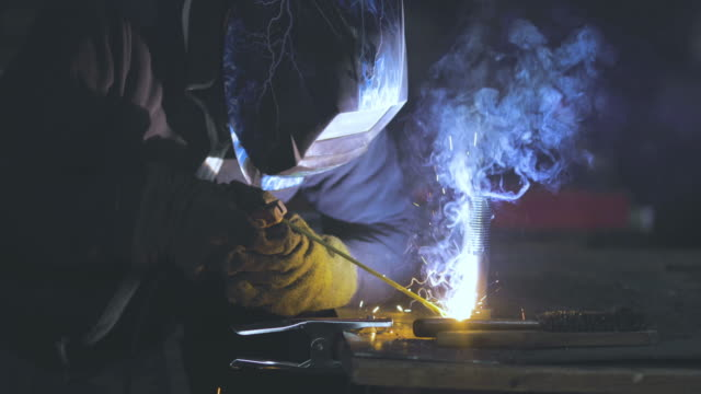 vídeos de stock e filmes b-roll de unrecognizable steel worker welding metal in a factory. - moedor