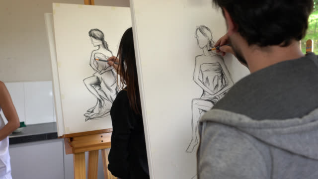 Unrecognizable students drawing on canvas with charcoal while looking at a female model video