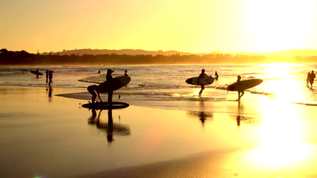 SLOW MOTION: Unrecognizable surf people enjoying summer evening surfing in ocean video