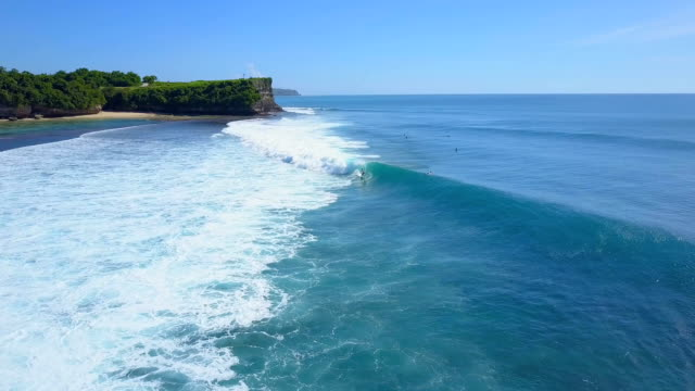 AERIAL: Unrecognizable surfer riding big foamy wave on Balangan beach, Bali video