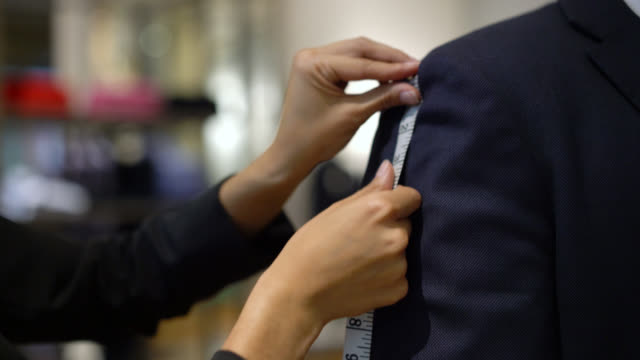 Unrecognizable tailor measuring the at length of the suit of a customer Close up of unrecognizable tailor measuring the at length of the suit of a customer instrument of measurement stock videos & royalty-free footage