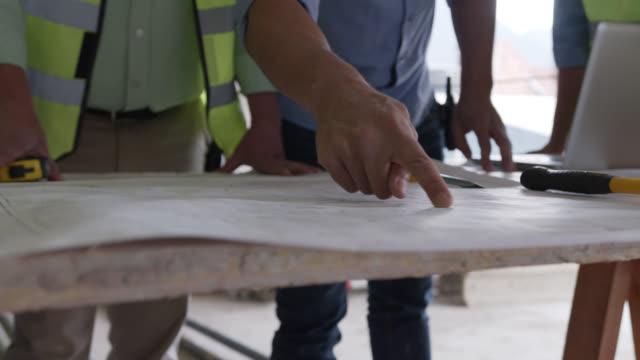 stockvideo's en b-roll-footage met onherkenbaar team van contractanten die een project bespreken dat op verschillende delen van een blauwdruk richt - hand pointing