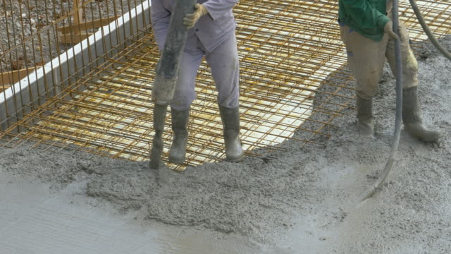 CLOSE UP: Unrecognizable team of workers pours fresh mortar over metal wiring.