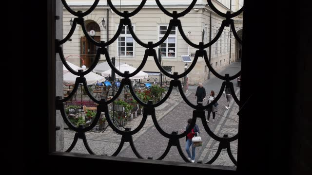 Unrecognizable tourists walk by pavement at Rynok square in Lviv. Shot through vintage grid window