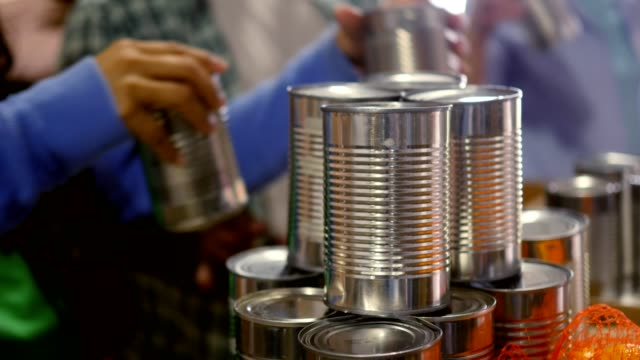 Unrecognizable volunteers stack canned food items for donation
