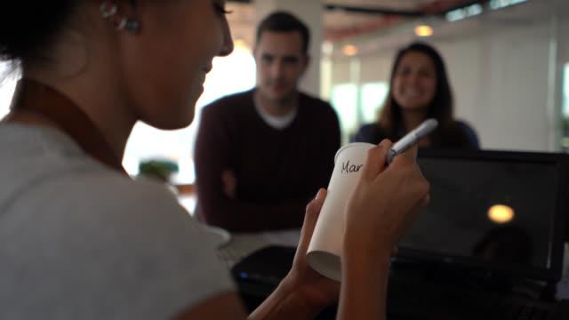 unkenntliche kellnerin schreibt eine nachricht über take-out-kaffee für kundenpaar in einem café - barista stock-videos und b-roll-filmmaterial