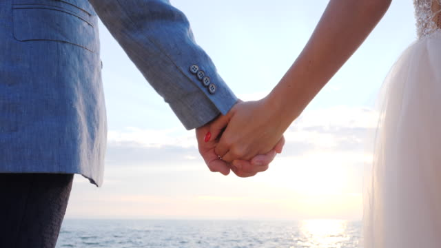 unrecognizable wedding couple holding hands on sunset or sunrise background. bride and groom standing outdoor near sea. sun flares. slow motion - young couple wedding friends video stock e b–roll