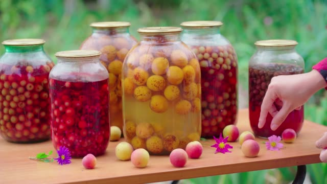 Unrecognizable woman arranges composition of fruits and flowers on table with canned juice. Close up of woman's hands create still-life outdoors