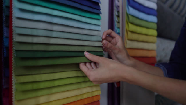 Unrecognizable woman at a textile store looking at fabric samples and textures Unrecognizable woman at a textile store looking at fabric samples and textures fabric swatch stock videos & royalty-free footage