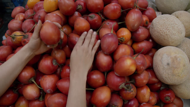 Unrecognizable woman grabbing tomato fruit from retail display at a farmer's market