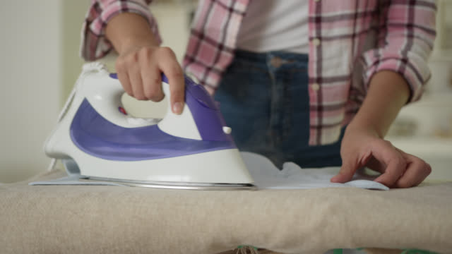 Unrecognizable woman ironing a men's button down shirt at home