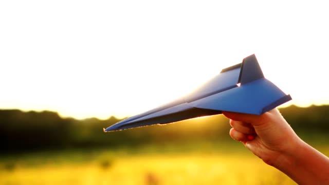 vídeos de stock, filmes e b-roll de mulher irreconhecível está brincando com avião de papel no pitoresco fundo do pôr do sol - braço humano
