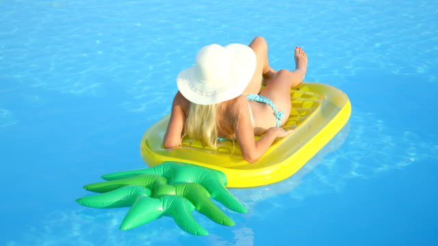 CLOSE UP: Unrecognizable woman laying on inflatable pineapple floatie in pool video