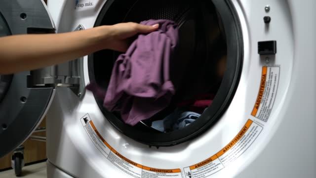 Femme méconnaissable, une machine à laver à une laverie automatique de chargement - Vidéo