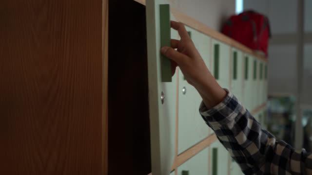 vídeos de stock, filmes e b-roll de mulher unrecognizable que põr afastado sua trouxa em um cacifo no escritório - armário com fechadura