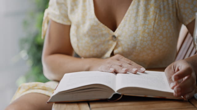 vidéos et rushes de slo mo femme méconnaissable lisant un livre à la table - décolleté