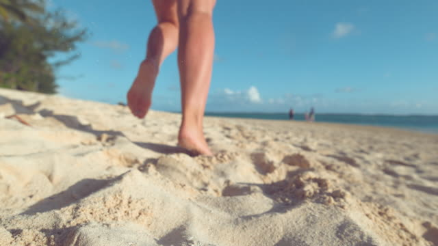 SLOW MOTION: Unrecognizable woman running in the summer sun along exotic shore. video