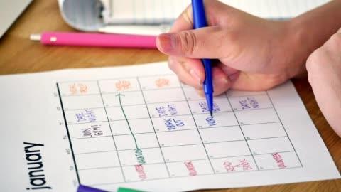 oigenkännlig kvinna schemalägger nyårslöften i sin kalender - dag bildbanksvideor och videomaterial från bakom kulisserna