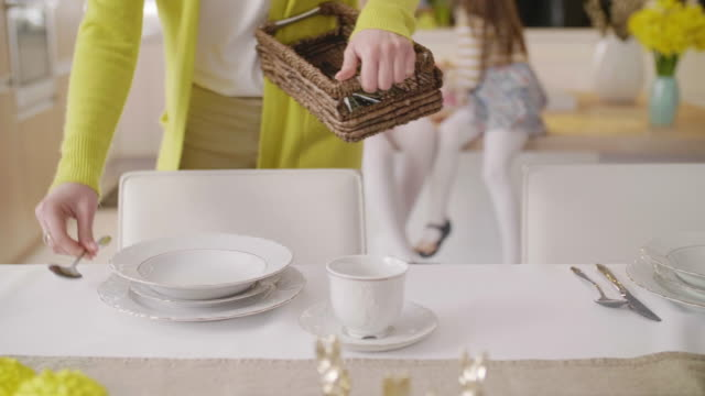 Unrecognizable woman setting the table