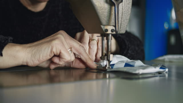 slo mo unrecognizable woman sewing medical masks at home - fatto in casa video stock e b–roll