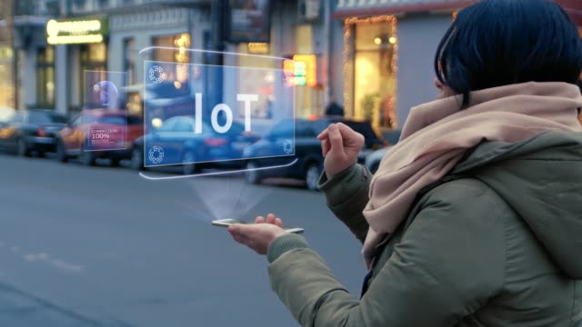 Unrecognizable woman standing on the street interacts HUD hologram with text IoT