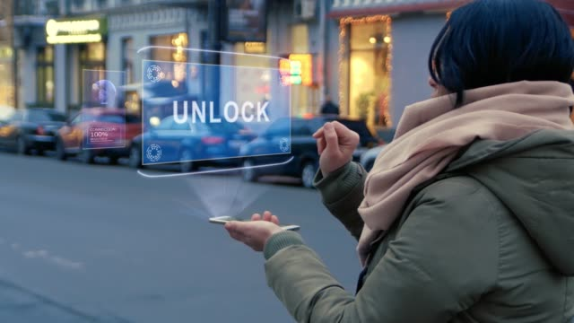 unrecognizable woman standing on the street interacts hud hologram with text unlock - serratura video stock e b–roll