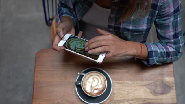 Irreconhecível mulher tirando uma foto de seu cappuccino com um smartphone - vídeo