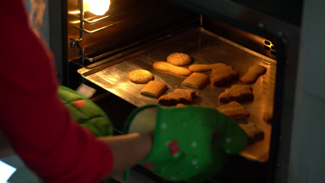 vídeos de stock e filmes b-roll de unrecognizable woman taking out christmas cookies from the oven on tray - christmas cookies
