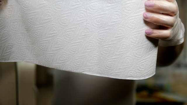 unrecognizable woman tearing off a piece of paper towel from roll. kitchen supplies. female hands taking a piece of white kitchen towel. processing, cleaning and sterilization concept. 4 k shot - rotolo video stock e b–roll