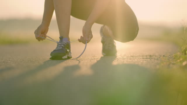 slo mo donna irriconoscibile che lega i lacci delle scarpe mentre fa jogging - annodare video stock e b–roll