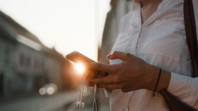cu tanınmayan kadın alacakaranlıkta şehirde bir akıllı telefon kullanarak - kulaklık seti ses ekipmanı stok videoları ve detay görüntü çekimi