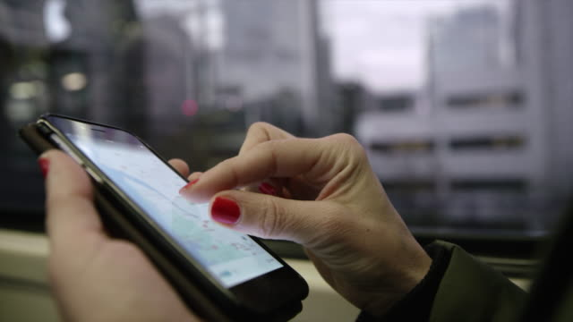 CU Unrecognizable woman using her smartphone on a train Close up shot of an unrecognizable woman checking a map on her smart phone while traveling on a train. London. UK. Shoot in 8K resolution. global positioning system stock videos & royalty-free footage