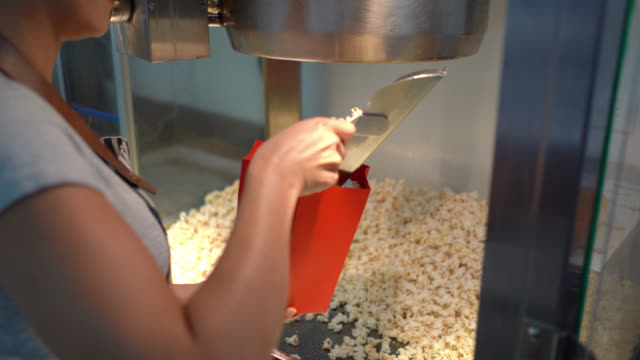 Unrecognizable woman working at the concession stand of a movie theatre serving pop corn