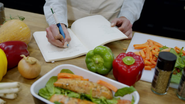 Unrecognizable woman writing down a recipe on notepad at the kitchen counter with delicious vegetables and food on foreground