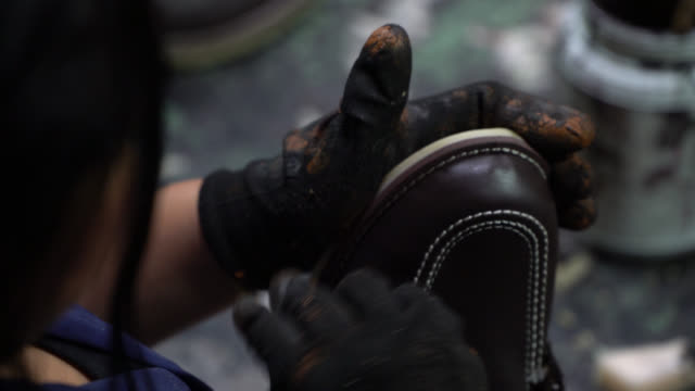 Unrecognizable worker polishing a shoe at a shoe factory Close up of unrecognizable worker polishing a shoe at a shoe factory shoe stock videos & royalty-free footage