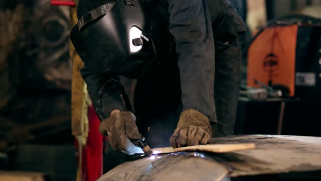Unrecognizable worker with welding helmet on cuts off metal piece with a oxy acetylene cutting torch at a mechanical hangar Unrecognizable worker with welding helmet on cuts off metal piece with a oxy acetylene cutting torch at a mechanical hangar. production line worker stock videos & royalty-free footage