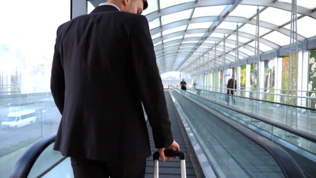 stockvideo's en b-roll-footage met onherkenbaar jonge zakenman lopen op roltrap in de hal van terminal en het dragen van koffer op wielen. succesvolle zakelijke persoon met bagage gaat binnen. concept reis of zakenreis. slow motion - zakenreis