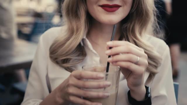 stockvideo's en b-roll-footage met onherkenbaar jonge kaukasische blonde vrouw, krullend haar, met sexy rode lippen en slimme horloge drinkt een alcoholische cocktail met een zwart rietje uit een grote bar glas in een restaurant op een stad straat. glimlachend en flirten op een date met een - stro