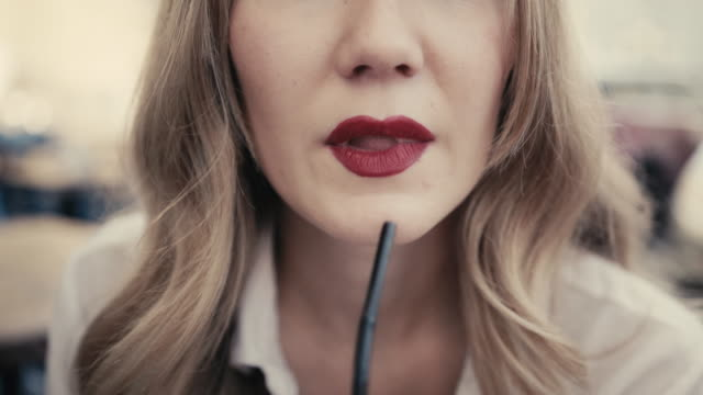 unrecognizable young caucasian blonde woman, curly hair, with sexy red lips drinks an alcoholic cocktail through a black straw from a large bar glass in a restaurant on a city street. concept of a sexy business lady, mistress. close up - paglia video stock e b–roll