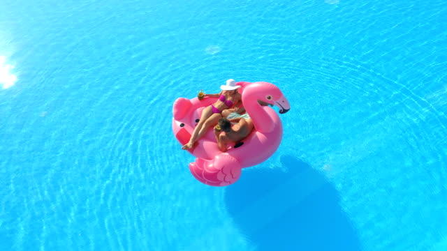 AERIAL: Unrecognizable young couple laying on flamingo floatie floating in pool video