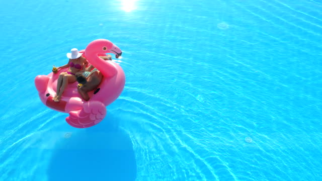 AERIAL Unrecognizable young couple sipping cocktails on flamingo floatie in pool
