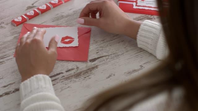 認識できない若い女性は、その中にバレンタインカードで封筒を開けます - バレンタイン チョコ点の映像素材/bロール