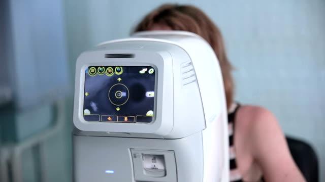 vidéos et rushes de méconnaissable jeune femme patient sur un examen de la vue. assistance médicale à l'optométriste dans une clinique moderne lumineuse - rétine