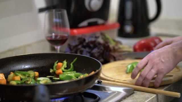 unrecognizable young man cutting vegetables and roasting them on pan - fornello video stock e b–roll