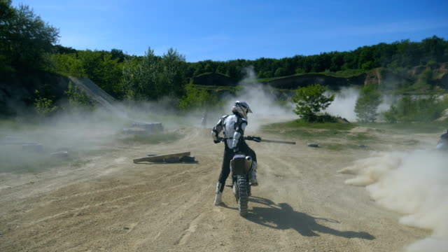 unrecognizable young man sitting at motocross bike, looking around and getting ready to ride. slow motion rear back view close up - bike tire tracks video stock e b–roll