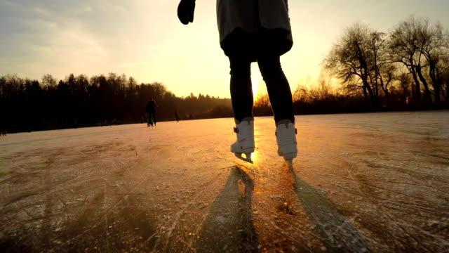 close up: unrecognizable young woman iceskating fast on big icy pond in park - łyżwa filmów i materiałów b-roll
